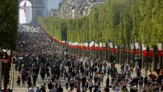 People walk on the car-free Champs-Elysees avenue in Paris (08 May 2016)