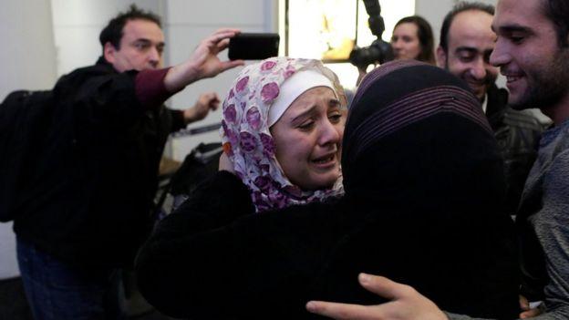 Una mujer musulmana saluda a su familia al llegar a Estados Unidos