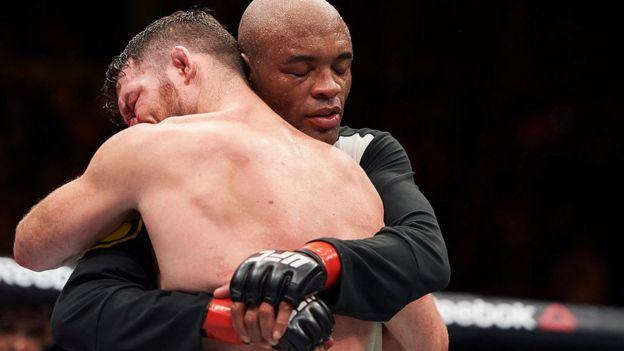 Boxeadores Michael Bisping y Anderson Silva abrazándose