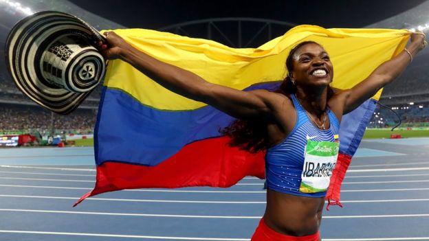 Caterine Ibargüen festeja con la bandera de Colombia