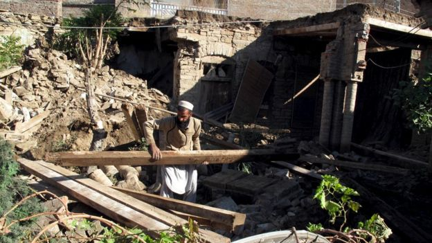 A man clears wooden beams from the rubble of a house after it was damaged by an earthquake in Mingora, Swat, Pakistan October 27, 2015.