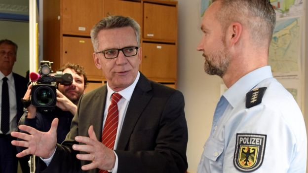 Mr de Maiziere at a police station, speaking to an officer 10 August 2016