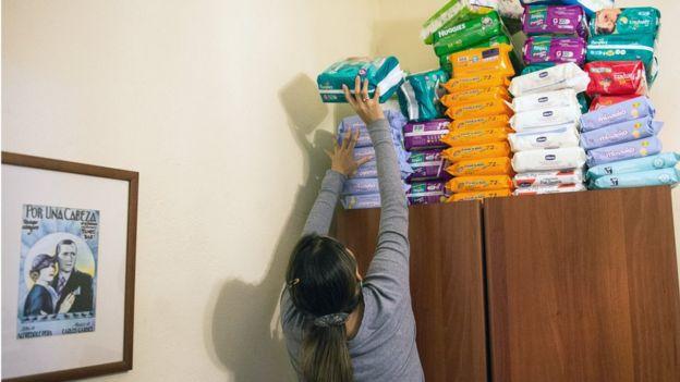 Una mujer alcanza uno de los muchos paquetes de pañales que guarda