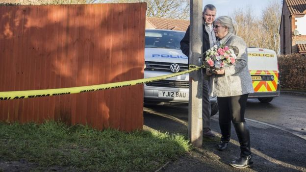 The grandmother of the young victim leaves a floral tribute at the scene near Alness Drive