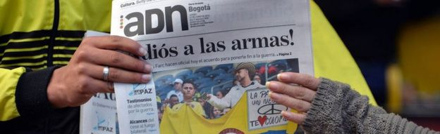 Colombians read newspapers with headlines about the ceasefire agreement between the government and the Farc in Bogota on June 23