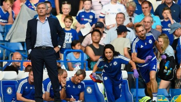 Chelsea manager Jose Mourinho looks on as team doctor Eva Carneiro rushes to treat Eden Hazard during the Barclays Premier League match between Chelsea and Swansea City at Stamford Bridge