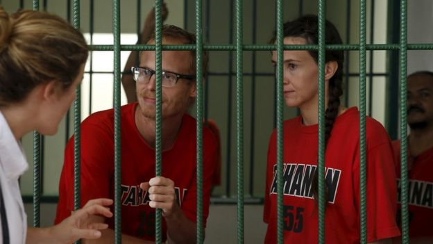 UK journalists Neil Bonner and Rebecca Prosser talk to their colleague from a cell before their trial at Batam district court in Indonesia on 19 October 2015