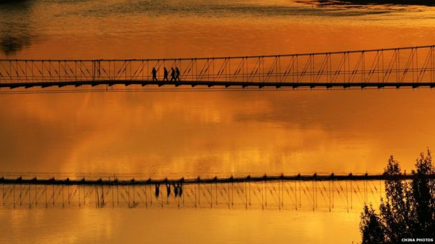Tourists walk on a hanging bridge above the Ertix River to view the sunset at the Wucai Shoal, or Colorful Shoal, a typical example of lava landform on 13 September 2007 in Buerjin County of Xinjiang Uygur Autonomous Region, China.