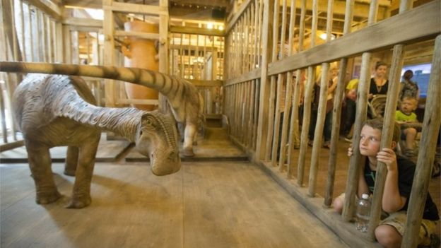 A visitor looks into a cage containing a model dinosaur inside a replica Noah's Ark at the Ark Encounter theme park