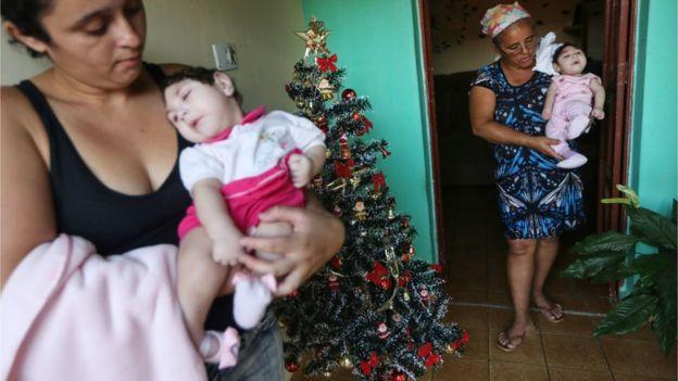 Raquel Barbosa e avó Maria José levam ao colo gêmeas Eloísa e Eloá, ambas de 8 meses e nascidas com microcefalia, em Areia, na Paraíba