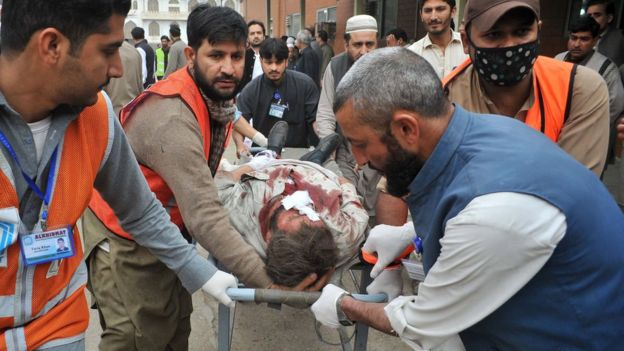 Pakistani volunteers move an injured blast victim to hospital