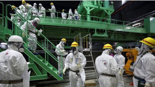 Members of the media and Tepco employees wearing protective suits and masks, near a fuel handling machine on the spent fuel pool inside the Number Four reactor building in the Fukushima Daiichi nuclear power plant, 7 November 2013.