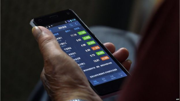 An investor checks stock prices on his smart phone at a securities company in Beijing on 9 July 2015.