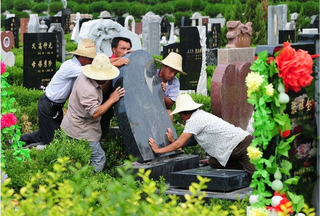 Cemetery workers put a tombstone in place at a cemetery in Tianjin, northern China on 20 July 2010.