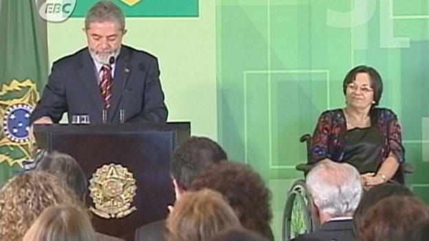 Maria da Penha onbserva enquanto então presidente Lula faz discurso após aprovação da lei pelo Congresso
