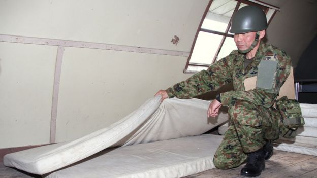 This handout picture provided by Hakodate Shimbun shows a Self-Defense Forces personnel showing inside of a house in a military exercise area in the town of Shikabe