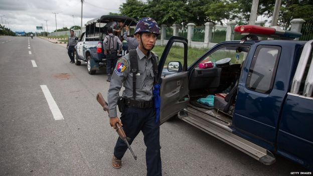 A policeman carries a rifle between waiting trucks outside of the gate of the USDP headquarters in Naypyitaw, Myanmar, 13 August 2015