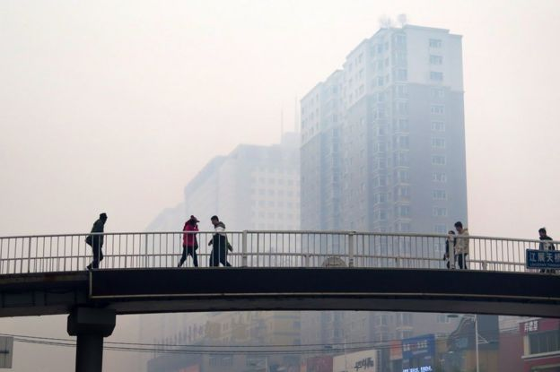 This picture taken on 8 November 2015 shows Chinese residents walking along a pedestrian bridge in Shenyang, China's Liaoning province