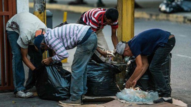 Personas buscando comida en la basura en una calle de Caracas.
