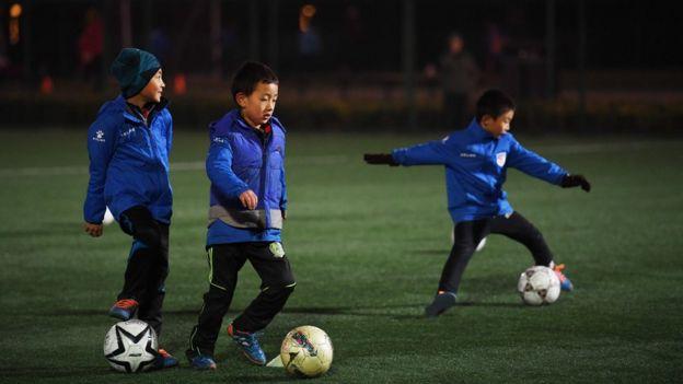 Crianças chinesas jogando futebol