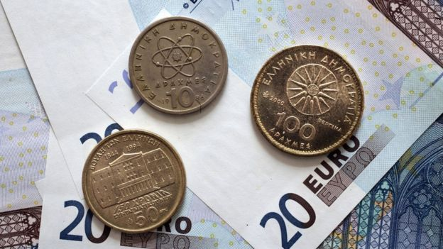 Greek Drachma coins sit on 20-Euro money notes
