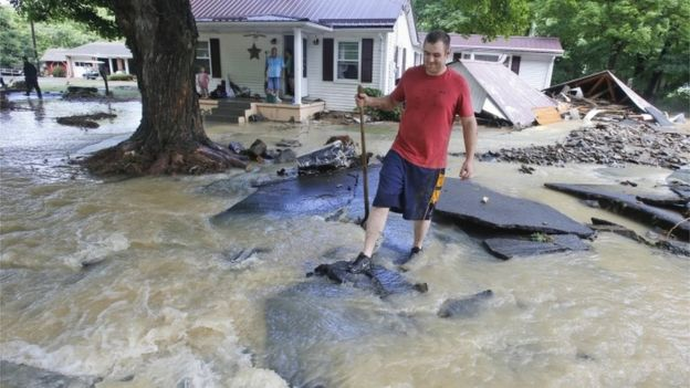 Mark Bowes, of White Sulphur Springs W. Va., makes his way to the road as he cleans up from severe flooding.
