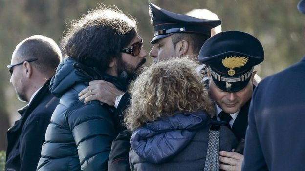 Giovanna Di Agostino, mother of Italian victim Fabrizia Di Lorenzo, and her son Gerardo, left, are hugged by authorities upon their arrival from Berlin with the coffin of her daughter Italian victim Fabrizia Di Lorenzo, at Rome