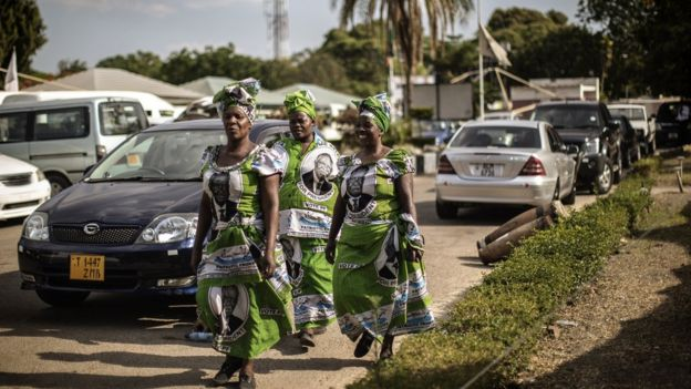 Women wearing dresses with the portrait of late Zambian President Michael Sata arrive at a memorial service in Lusaka, Zambia, on November 10, 2014, on the eve of Sata's State funeral