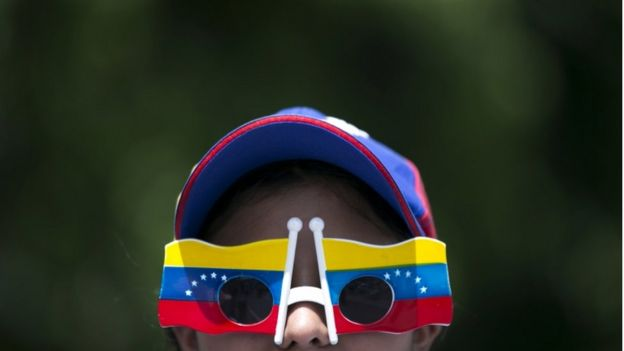 A woman wears Venezuelan flag motif glasses during a protest demanding a recall referendum against Venezuela