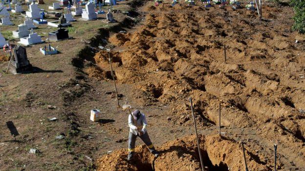 Homem abre cova onde foram enterrados presos mortes em chacina em Manaus