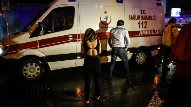 Una mujer y un hombre caminan junto a una de las ambulancia enviadas para asistir a las víctimas del ataque.