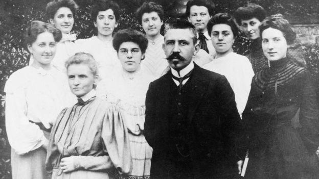 Marie Curie y Paul Langevin adelante con un grupo de mujeres atrás.
