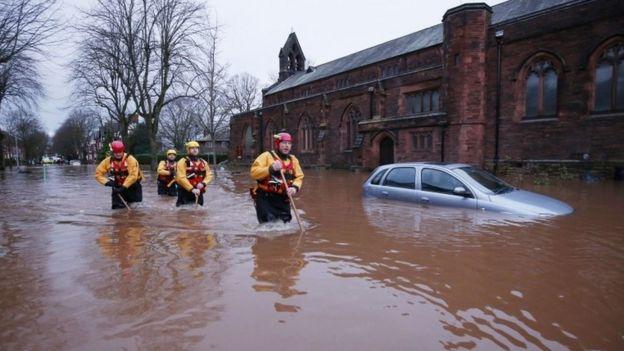 Emergency workers walk through floodwater on Warwick Road in Carlisle