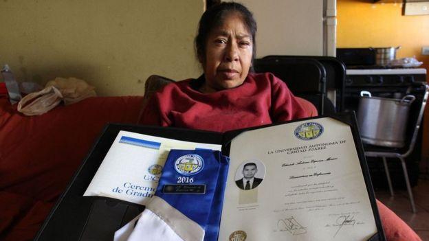Patricia Moreno sostiene en sus manos el diploma de enfermería de su difunto hijo.