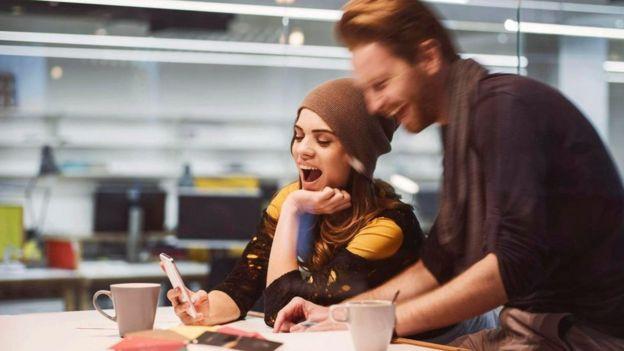 Dos jóvenes una oficina que hablan y se ríen