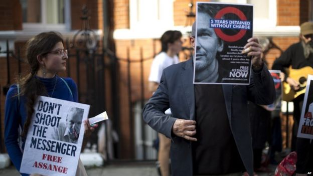 Supporters of WikiLeaks founder Julian Assange hold placards during a vigil across the street from the Ecuador embassy in London, Friday 19, June 2015