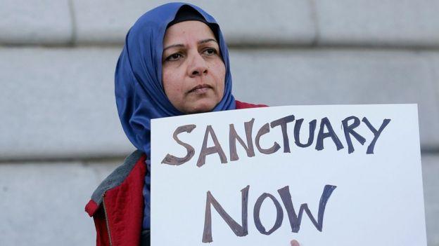 Una mujer musulmana sostiene un cartel que dice