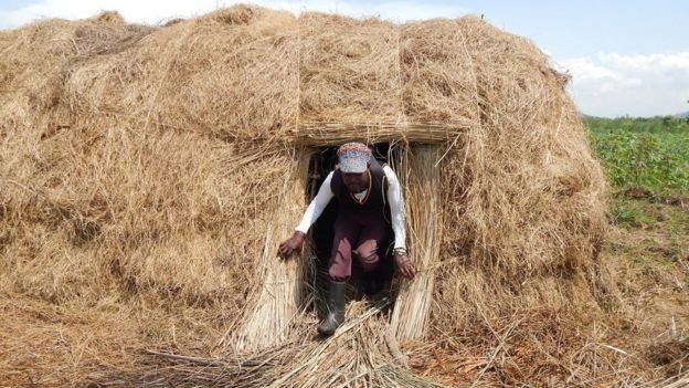 Man coming out of grass house