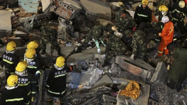 Rescuers search for survivors among debris after a residential building collapsed in Wuyang county, Henan province, China October 30, 2015.