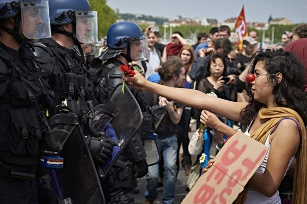 A protester faces police with a bouquet of flowers in Lyon, 26 May