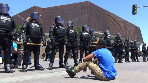 A protestor sits in front of a cordon of riot police at a Donald Trump rally in Fresno, California