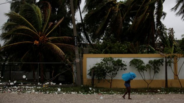 A woman protects herself from rain with an umbrella ahead of Hurricane Matthew in Les Cayes, Haiti