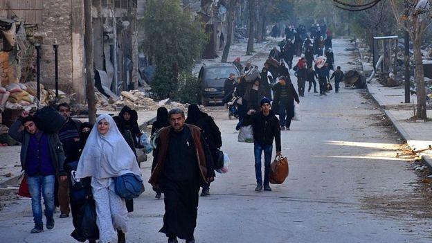 Syrian residents evacuate eastern Aleppo through Bab al-Hadid district on 7 December 2016