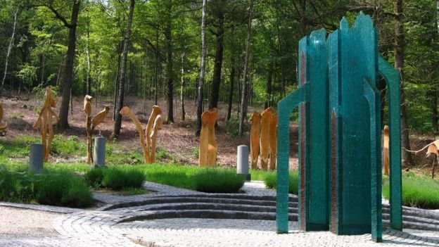 Un pequeño monumento verde situado cerca de árboles en Viroinval