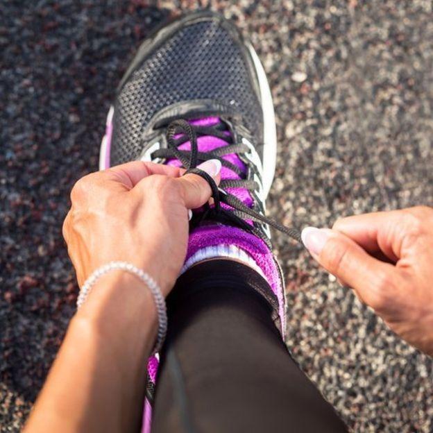 Mujer atándose las zapatillas