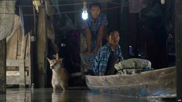 Residents look out from a monastery submerged by floodwaters in Kyouk Ye village near Hinthada town in Irrawaddy region on 6 August 2015