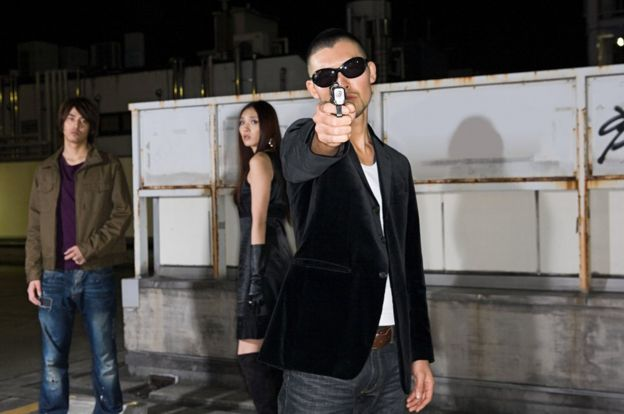 模特擺拍。現在就連日本黑幫也很少用槍。