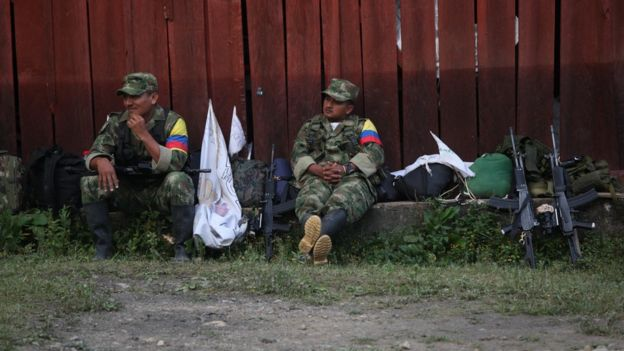 Guerrilleros sentados, cerca de unos fusiles.