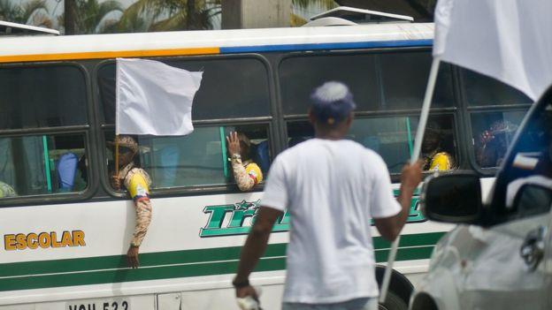 Combatientes de las FARC saludan desde un autobús a un hombre vestido de civil que sostiene una bandera blanca.