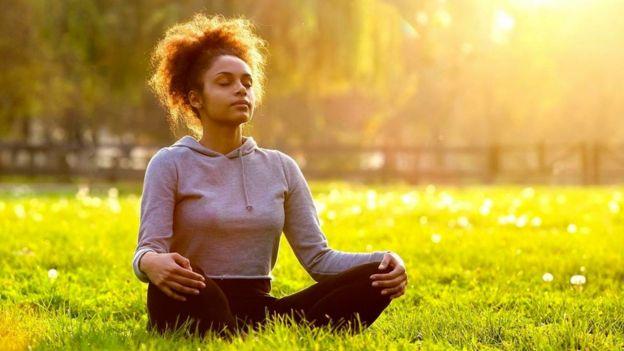 Una persona meditando en un parque